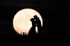 Пары целуя в луне Стоковые Изображения