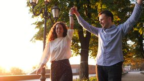 Пары человека и женщины бежать держащ руки в городе осени паркуют Стильная пара или студенты в деле одевают счастливое к сток-видео