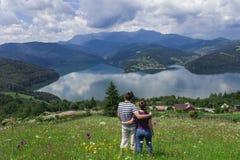 Пары человека и женщины наслаждаясь красивыми озером и горой стоковое фото rf