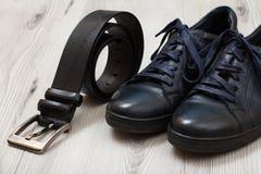 Пары черных кожаных ботинок ` s людей и кожаного пояса для людей на gr Стоковая Фотография