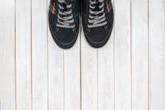 Пары черных тапок на белой деревянной предпосылке Стоковое Фото