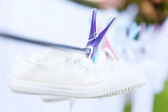 Пары чистых белых тапок повиснули на веревочке засыхания прачечной вдоль других blured деталей в задней части закрепленной с фиол Стоковая Фотография