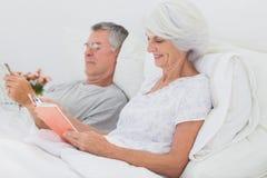 Пары читая совместно в кровати Стоковая Фотография RF