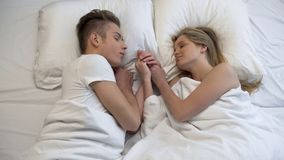 Пары штрихуя руки лежа в кровати, за сладкий момент одина другого до времени ложиться спать стоковое изображение rf