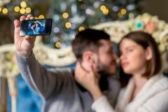 Пары любовников принимая selfie на smartphone во времени рождества Стоковое Изображение RF
