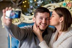Пары любовников принимая selfie на smartphone во времени рождества Стоковое Фото