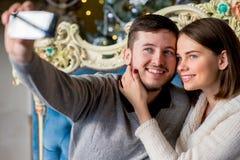 Пары любовников принимая selfie на smartphone во времени рождества Стоковое фото RF