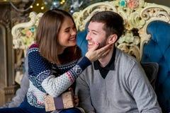 Пары любовников сидя на софе время конца рождества предпосылки красное вверх Стоковые Изображения