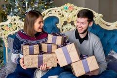 Пары любовников сидя на софе время конца рождества предпосылки красное вверх Стоковая Фотография