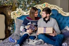 Пары любовников сидя на софе время конца рождества предпосылки красное вверх Стоковые Фотографии RF