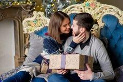 Пары любовников сидя на софе время конца рождества предпосылки красное вверх Стоковые Изображения RF