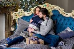 Пары любовников сидя на софе время конца рождества предпосылки красное вверх Стоковое Фото