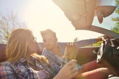 Пары любовников управляя на обратимых автомобильных новобрачных спаривают на романтичной дате стоковое изображение rf