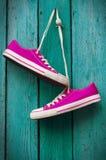 Пары ярких розовых тапок вися на шнуре Стоковое Фото