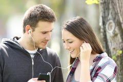 Пары flirting и деля музыка outdoors Стоковые Изображения RF