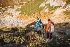 Пары hikers в горах Туристы женщина и человек спускают от горы Стоковое фото RF