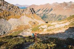 Пары hikers в горах Туристы спускают от горы Стоковое Изображение