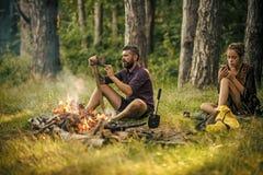 Пары hikers ослабляют на костре в лесе Стоковая Фотография RF