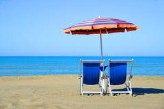 Пары loungers солнца и зонтика навеса на пляже Стоковые Фото