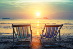 Пары loungers солнца на пляже во время захода солнца Природа Стоковая Фотография