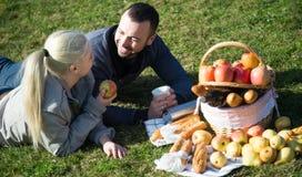 Пары lounging на пикнике outdoors Стоковое Изображение