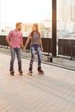 Пары rollerblading и держа руки Стоковое Фото