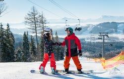 Пары snowboarders на верхнем лыжном курорте на солнечном дне стоковые фото