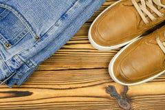 Пары tan цвета, кожаных тапок и джинсов на деревянной предпосылке, взгляд сверху с космосом экземпляра Стоковые Фотографии RF