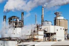Пар и дым испуская от промышленной дымовой трубы i фабрики Стоковые Изображения