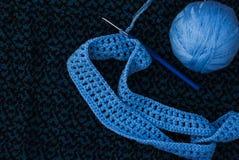 Пасмо голубого потока с крюком и начало связать на предпосылке knitwear скопируйте космос стоковая фотография
