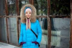 Пасмурный внешний портрет зимы молодой счастливой прелестной женщины в ярком cyan пальто представляя в парке города зимы против б Стоковые Изображения RF
