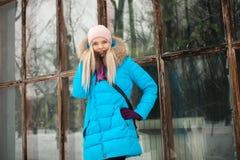 Пасмурный внешний портрет зимы молодой счастливой прелестной женщины в ярком cyan пальто представляя в парке города зимы против б Стоковое Изображение RF