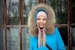Пасмурный внешний портрет зимы молодой счастливой прелестной женщины в ярком cyan пальто представляя в парке города зимы против б Стоковые Изображения