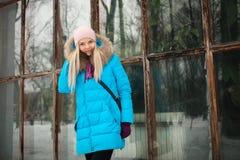 Пасмурный внешний портрет зимы молодой счастливой прелестной женщины в ярком cyan пальто представляя в парке города зимы против б Стоковое фото RF
