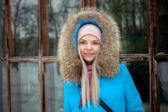 Пасмурный внешний портрет зимы молодой счастливой прелестной женщины в ярком cyan пальто представляя в парке города зимы против б Стоковая Фотография