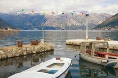 Пасмурный среднеземноморской ландшафт с снег-покрытыми горами и рыбацкими лодками в малой гавани Черногория, залив Kotor Стоковые Изображения