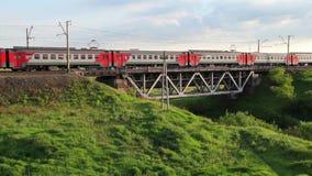 Пассажирский поезд пропуская над железнодорожным мостом на заходе солнца акции видеоматериалы