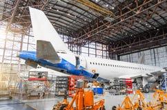 Пассажирский самолет на обслуживании ремонта двигателя, среди jacks, взгляда кабеля и зада фюзеляжа в авиапорте ha Стоковые Изображения RF