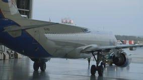 Пассажирский самолет, обслуживая двигатели и ремонт фюзеляжа, покидая ангар авиапорта Аэробус для ремонта стоковые изображения