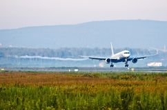 Пассажирский самолет перед касающей посадкой взлётно-посадочная дорожка при vortexes приходя от wingtips Стоковые Фотографии RF