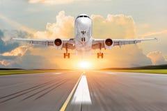 Пассажирский самолет принимает от взлётно-посадочная дорожка перед светом от солнечности стоковая фотография