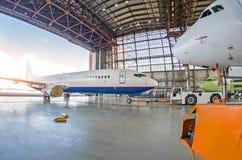 Пассажирский самолет с поврежденным двигателем нажим свертывает вверх трактор кудели к ангару для ремонта, обслуживания стоковые изображения rf