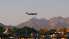 Пассажирский самолет в посадке неба на предпосылке гор и пальм в Египте акции видеоматериалы