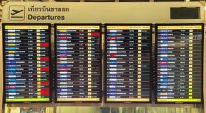 Пассажиры БАНГКОКА - 4-ое апреля проверяя расписание полетов на диаграммах авиапорта на авиапорте Suvarnabhumi, 4-ого апреля 2014 Стоковое Фото