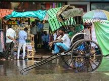 Пассажиры водителя рикши ждать на улице в Kolkata, Индии стоковое изображение
