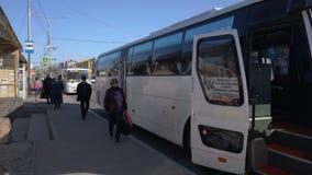 Пассажиры вписывают космос Hyundai белой междугородной шины Aero высокий на автобусную остановку акции видеоматериалы