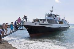 Пассажиры всходя на борт от деревни Praskoveevka пляжного комплекса на коралле корабля Gelendzhik, зона Краснодара, Россия Стоковые Изображения RF