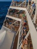 Пассажиры выравнивают палубы туристического судна на отклонении от порта стоковое фото