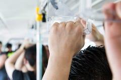 Пассажиры держа рельс руки на толпить общественных транспортах стоковая фотография