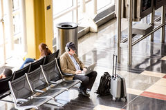 Пассажиры ждать перед ярким внутренним окном авиапорта Стоковые Изображения
